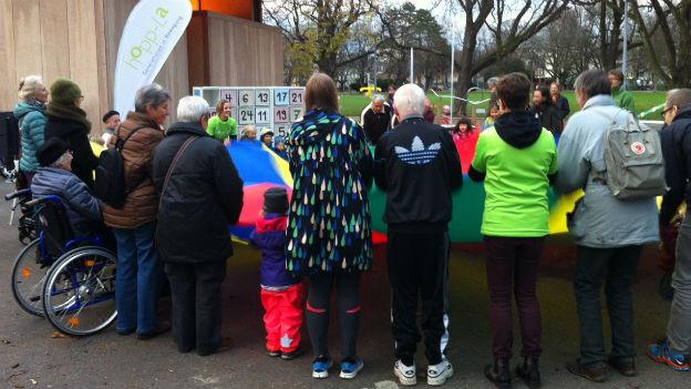 Senioren und Kinder spielen mit dem Schwungtuch im Schützenmattpark in Basel.
