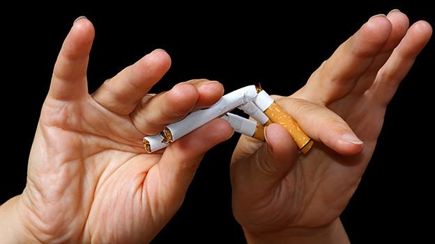Hände die ein paar Zigaretten zerbrechen.