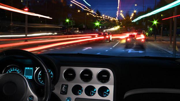 Ein Auto im nächtlichen Verkehr mit vielen Lichtern vorne, rechts und links.
