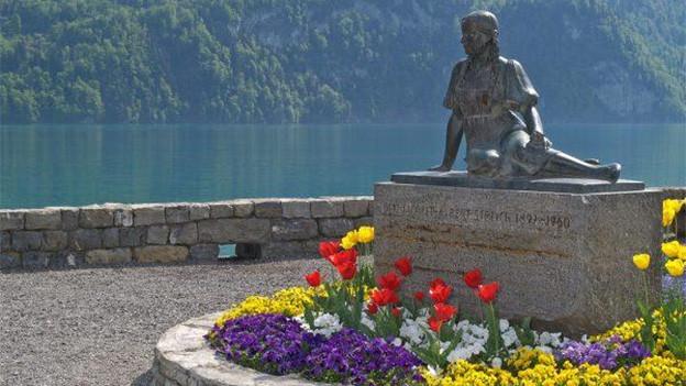 Eine Steinskulptur mit einer sitzenden jungen Frau.