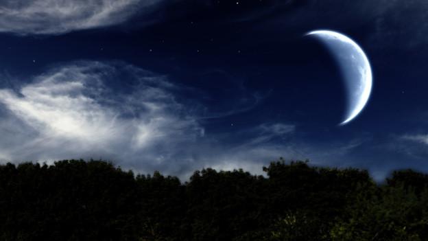 Nächtliche Stimmung mit Sichelmond am Himmel mit ein paar wenigen Wolken.