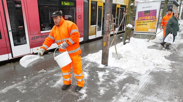 Mann salzt Bushaltestelle.