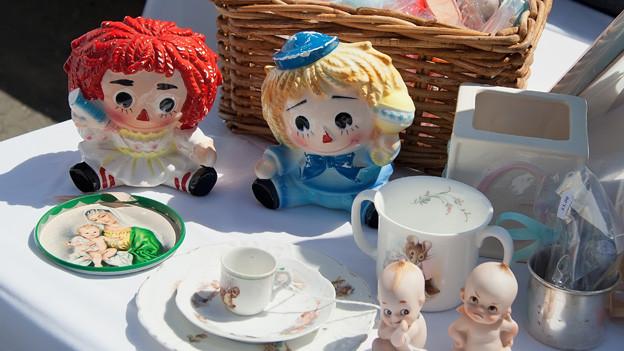 Porzellanpuppen und -teller vor einem Weidenkorb auf einem Tisch.