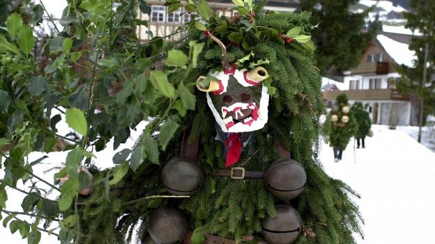 Furchteinflössender Silvesterchlaus mit Tannenzweigen als Kleid.