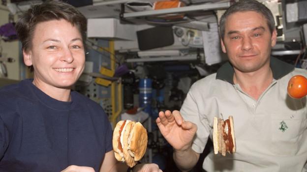 Zwei Astronauten mit schwebenden Burgern.