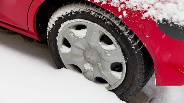 Der Reifen eines roten Autos steckt im Schnee.