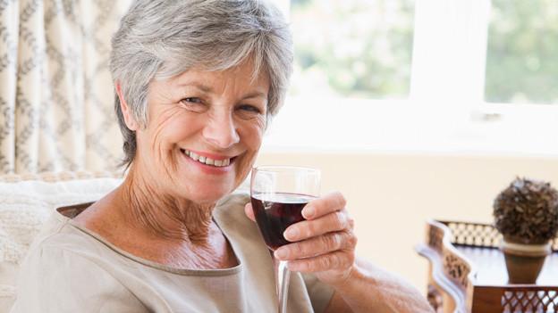 Eine ältere Dame sitzt vor dem Fenster auf einem Sofa und gönnt sich ein Glas Wein.