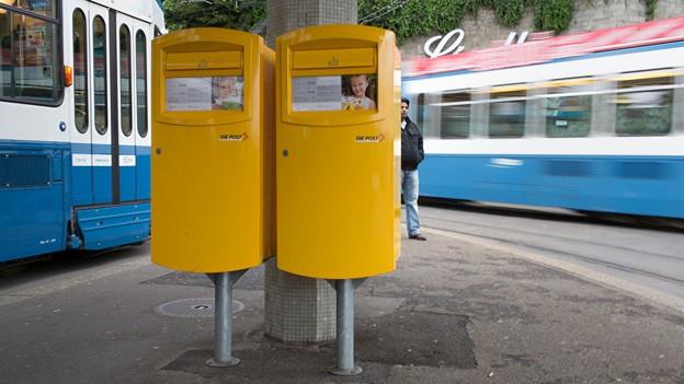 Zwei gelbe Briefkasten an einer Tramhaltestelle in Zürich.