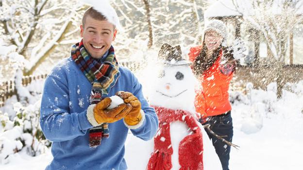 Ein junges Paar bewirft sich im Garten mit Schneebällen.
