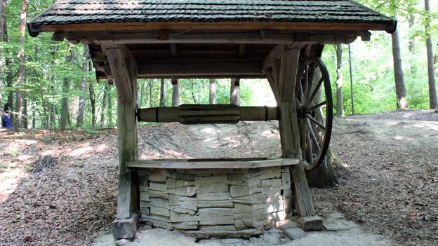 Ein gemauerter Ziehbrunnen mit einem Holzdach und einer Seilwinde.