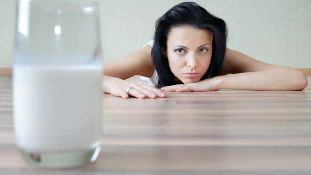 Eine junge Frau liegt bäuchlings auf dem Boden, etwas entfernt von ihr steht ein Glas Milch.
