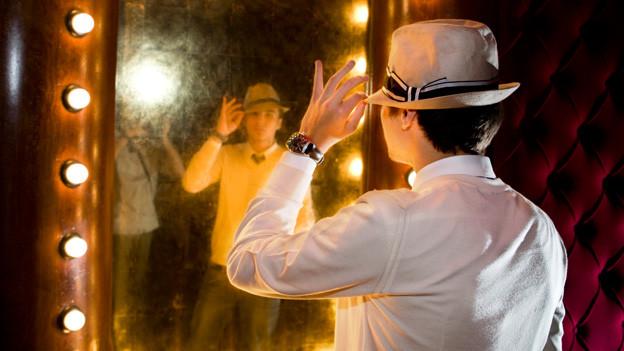 Ein junger Mann mit Hut vor einem mit Glühbirnen beleuchteten Garderobenspiegel.