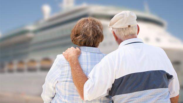 Ein älteres Ehepaar steht mit dem Rücken zum Fotografen vor einem grossen Kreuzfahrtschiff.