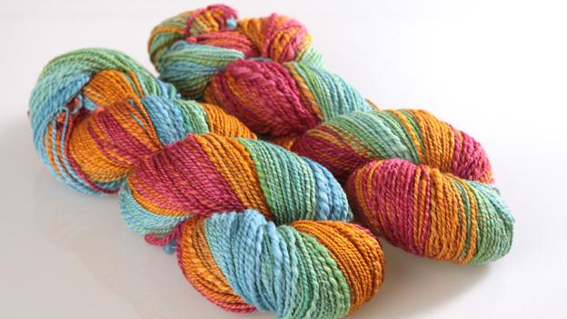Zwei Wollknäuel-Zöpfe die verschiedene Farben enthalten.