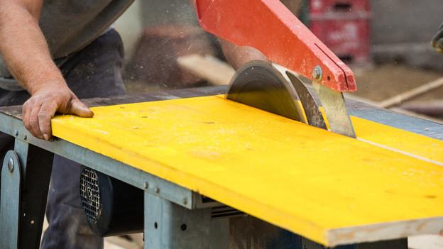Ein Bauarbeiter schneidet unter einer grossen Säge eine gelbe Holzplatte in zwei Stücke.