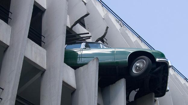 Die Kühlerhaube eines grünen Autos hängt auf den durchbohrten Säulen eines Parkhauses.