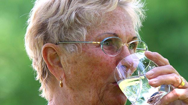 Seniorin trinkt ein Glas Wasser.