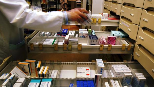 Ein Apotheke nimmt eine Schachtel mit Pillen aus einer Schublade voller Medikamente.