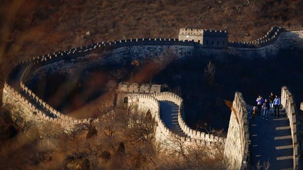 Die hohe und dicke Mauer windet sich kilometerweit über Hügel und durch Täler.