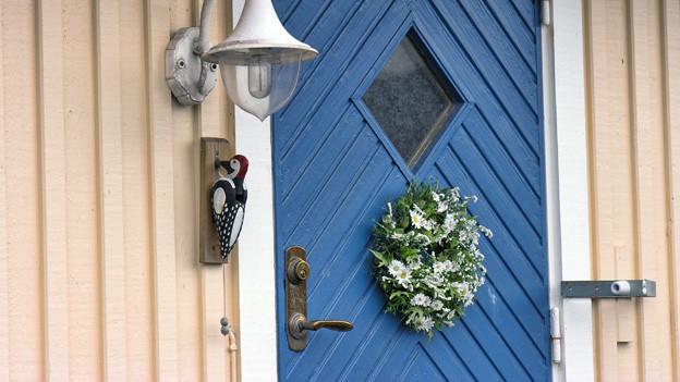 Eine blaue Haustür mit einem Specht aus Holz, der als Klingel dient.