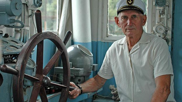 Kapitän vor Steuerrad.