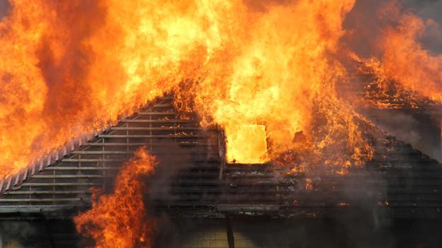 Flammen lodern aus dem Dachstock eines brennenden Hauses.