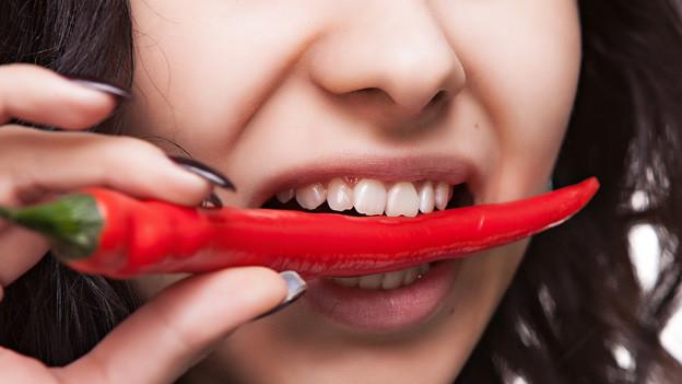 Eine Frau mit einer Chilischote zwischen den Zähnen.