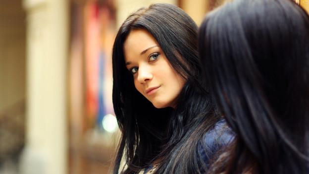 Spiegelbild einer jungen Frau mit dunklen Haaren.