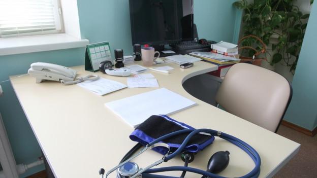 Blick auf den Schreibtisch eines Arztes. Stethoskop liegt bereit. Computer ist ausgeschaltet.