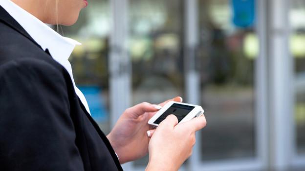 Eine Frau liest eine Nachricht auf ihrem Smartphone.