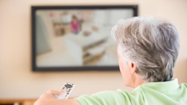 Eine ältere Frau sitzt auf dem Sofa mit Blick auf den Fernseher, der an der Wand hängt.