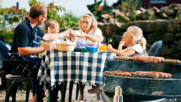 Eine Familie sitzt auf der Terrasse und geniesst ein Essen mit auf dem Grill gebratenem Fleisch.