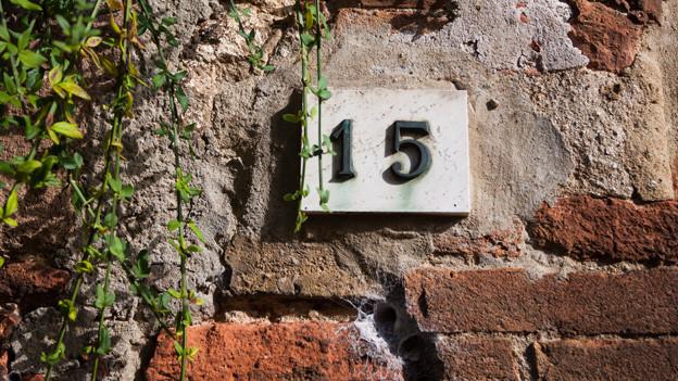 Ein Schild mit der Nummer 15 an einem alten Backsteinhaus.