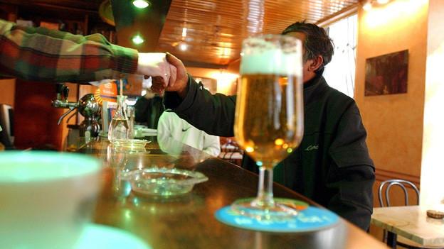 Ein Blas Bier auf der langen Theke einer Bar.