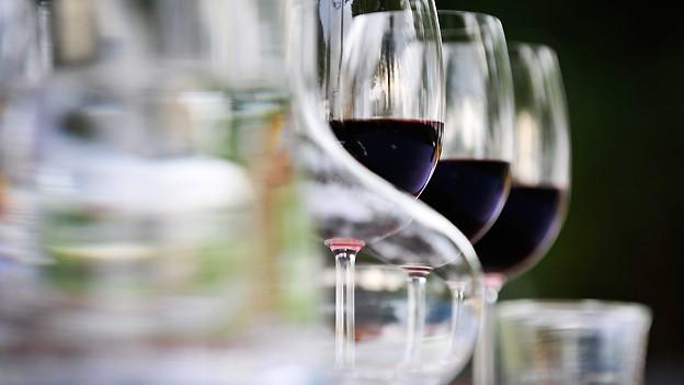 Glaskaraffe mit Wasser neben gefüllten Weingläsern.