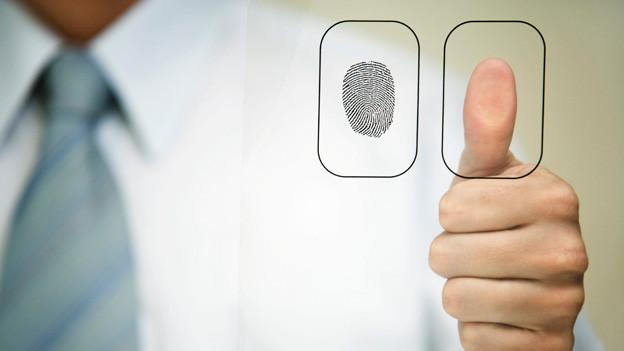 Eine Männerhand hält einen Finger für einen Abdruck auf ein Glas.