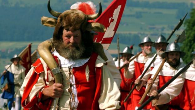 Delegation aus Niedwalden bei der Jahresfeier der Schlacht bei Sempach 2002. Die Gruppe trägt historische Kostüme mit Fellmützen, Stierhörner, Helmen und Hellebarden.