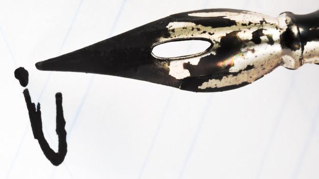 Füllfederhalter schreibt «i» auf Papier.
