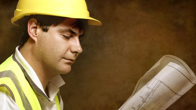 Ein Bauarbeiter mit gelbem Schutzhelm und Leuchtweste liest einen Bauplan.