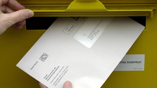 Ein Stimmcouvert wird in einen gelben Briefkasten geworfen.