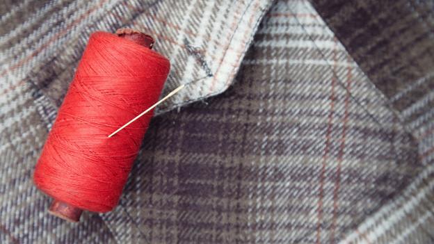 Eine grosse Spule mit rotem Faden liegt auf einem karierten Flanellhemd.