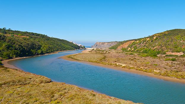 Ein breites Flussbett in einer kargen Landschaft.