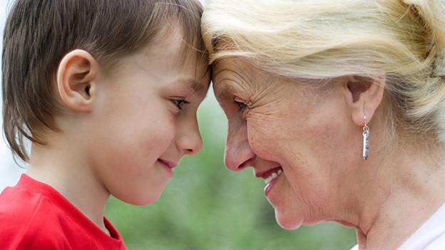 Ein Bub steht lachend Stirn an Stirn mit seiner Oma.