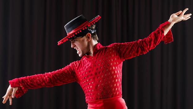 Ein Flamencotänzer mit schwarzem Hut und rotem Hemd.