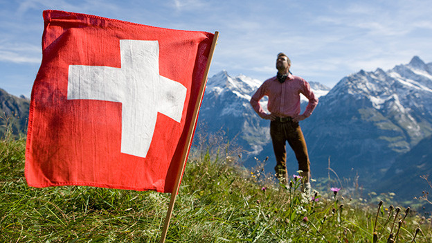Ein Mann steht in den Bergen vor einer Schweizer Flagge.