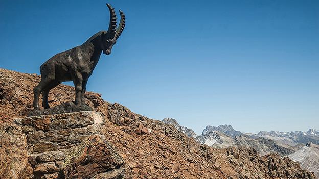Eine Steinbock-Statue in einer felsigen Landschaft.