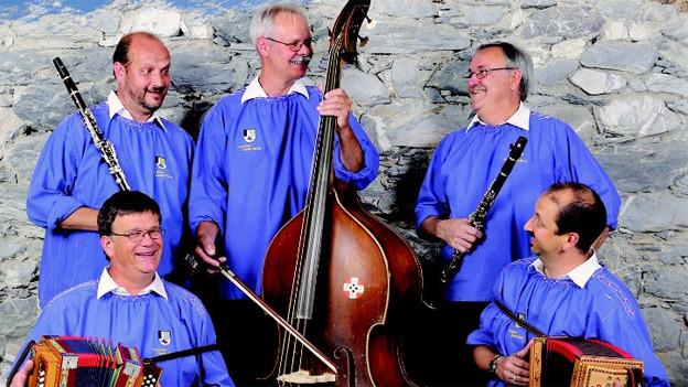 Fünf Musikanten in blauen Sennenkutten, die mit ihren Instrumenten vor einer Steinmauer stehen.