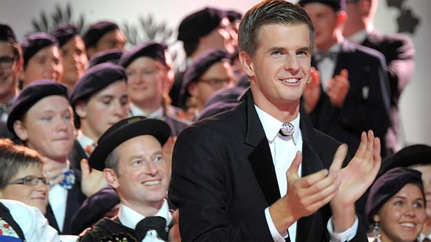 Der Moderator steht vor einer Gruppe von Jodlerinnen und Jodlern und applaudiert.