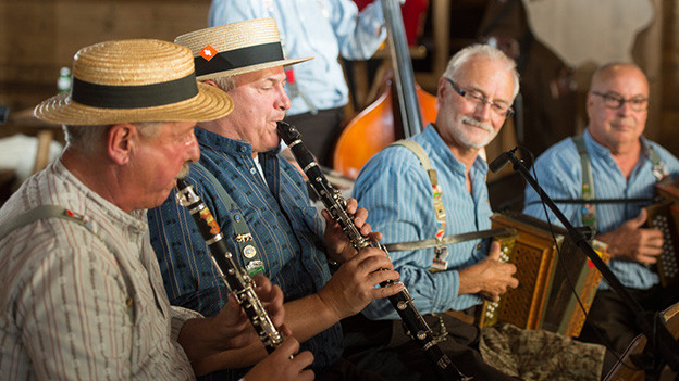 Fünf Musikanten einer Ländlerformation mit Klarinetten, Schwyzerörgeli und Kontrabass.