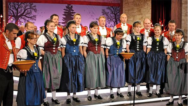 Die Frauen und Männer des Jodelchors tragen bunte Appenzeller Trachten.